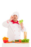 Happy chef holding leaf of salad and cooking with fresh vegetabl Royalty Free Stock Photos