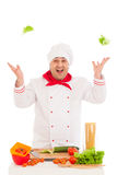 Happy chef holding leaf of salad and cooking with fresh vegetabl Stock Images