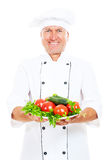 Happy chef holding plate with vegetables Royalty Free Stock Photos