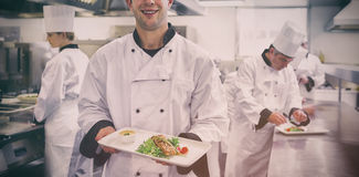 Happy chef holding salmon dish. In kitchen Stock Photography