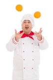 Happy chef holding two oranges wearing red and white uniform Royalty Free Stock Photo