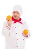 Happy chef holding two oranges wearing red and white uniform Royalty Free Stock Images