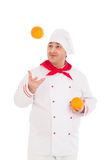 Happy chef holding two oranges wearing red and white uniform Royalty Free Stock Image