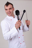 Happy chef holding various kitchen utensils Stock Image