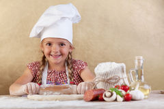 Happy chef little girl stretching the dough Stock Images