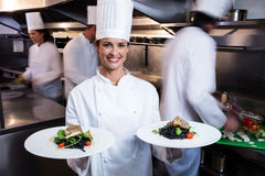 Happy chef presenting her food plates Stock Photo