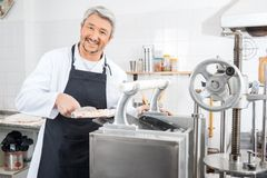 Happy Chef Processing Ravioli Pasta In Machine Royalty Free Stock Images