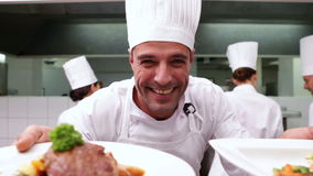 Happy chef showing two dishes to camera stock footage