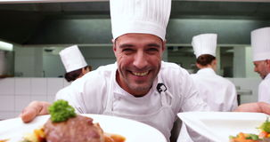 Happy chef showing two dishes to camera. In a commercial kitchen stock video