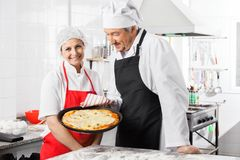 Happy Chef Standing By Colleague Holding Pizza Pan Royalty Free Stock Photos