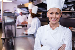 Happy chef standing in commercial kitchen in a restaurant. Happy chef standing in commercial kitchen and three chefs discussing In background stock images