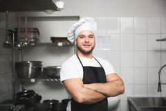 Happy chef standing in kitchen royalty free stock image