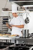 Happy Chef Using Digital Tablet In Kitchen. Happy male chef using digital tablet with pasta dishes at commercial kitchen counter Royalty Free Stock Image