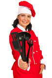 Happy chef woman giving kitchen utensils Royalty Free Stock Images