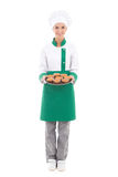 Happy chef woman in uniform holding tray with muffins - full len. Gth isolated on white background Royalty Free Stock Photography