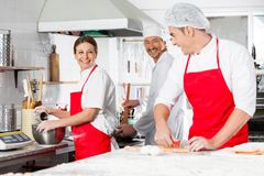 Happy Chefs Conversing In Commercial Kitchen Stock Images