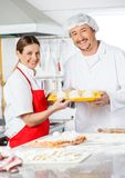 Happy Chefs Holding Pasta Tray In Kitchen Stock Images