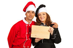 Happy chefs holding wooden board Royalty Free Stock Photo