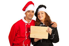 Happy chefs holding wooden cutting board Stock Photography