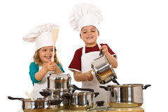 Happy chefs making noise. Happy kid chefs making noise banging the cooking pots with wooden spoons - isolated Stock Image