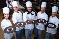 Happy chefs presenting their dessert plates. In commercial kitchen Royalty Free Stock Photos
