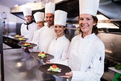 Happy chefs presenting their food plates Stock Image