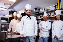 Happy chefs team standing together in commercial kitchen Stock Image