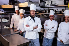 Happy chefs team standing together in commercial kitchen Royalty Free Stock Photos