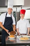 Happy Chefs With Variety Of Sweet Dishes Royalty Free Stock Photo