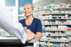 Happy Chemist Looking At Customer In Pharmacy. Happy female chemist looking at male customer in pharmacy stock photo