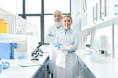 Happy chemists in white coats standing in chemical laboratory with microscopes and flasks Stock Image