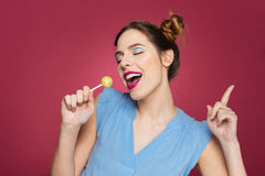 Happy cherming young woman with lollipop dancing and singing. Over pink background stock images