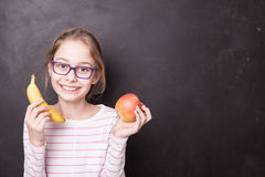 Happy chid girl with apple and banana at the chalkboard Stock Photography