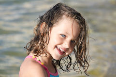 Happy child. A happy young girl with blue eyes and a gorgeous smile and sand in her wet hair Stock Photography