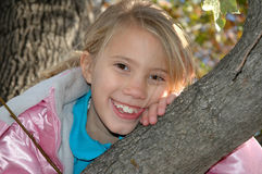 Happy Child. An eight year old girl climbs up in a tree. A head shot of a beautiful little girl leaning on the branch of a tree Stock Photos