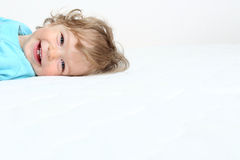 Happy child. Smiling happy child on white bed royalty free stock photos