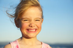 Happy child. Little girl making a funny face at the beach stock image