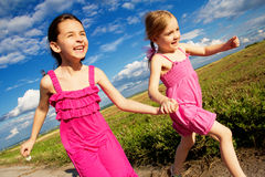 Happy child. Group children running across green grass outdoor Stock Image