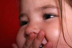 Happy Child. Extreme closeup of childs laughter, covering her mouth with her hand royalty free stock images