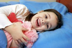 Happy child. Little six year old girl laughs laying in her bed, holding her favourite toy, with an expression of innocence Royalty Free Stock Photography