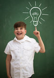 Happy child against blackboard with drawing light bulb idea Royalty Free Stock Photography