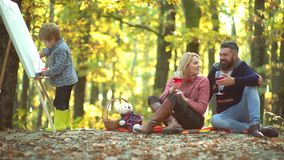 Happy child artist drawing picture on autumn nature. Family parenthood and people concept - happy mother father and stock footage