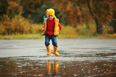 Happy child baby boy with rubber boots jump in puddle on autumn Stock Photo