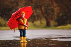 Happy child baby boy with rubber boots and umbrella jump in pudd. Le on an autumn walk stock photo