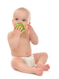 Happy child baby boy sitting in diaper and eating green apple Royalty Free Stock Photos
