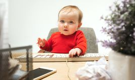 Happy child baby girl toddler sitting with keyboard of computer isolated on a white background. Happy child baby girl sitting with keyboard of modern computer or Royalty Free Stock Photos