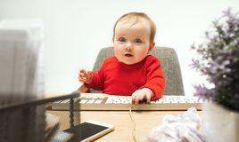 Happy child baby girl toddler sitting with keyboard of computer isolated on a white background. Happy child baby girl sitting with keyboard of modern computer or Stock Photography