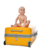 Happy child baby toddler sitting on yellow plastic travel suitca. Happy infant baby toddler sitting on yellow plastic travel suitcase on wheels getting ready for Stock Photos