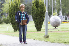 Happy child with a backpack and books go to school. Outdoor. Royalty Free Stock Photography