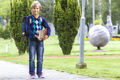 Happy child with a backpack and books go to school. Outdoor. Royalty Free Stock Image